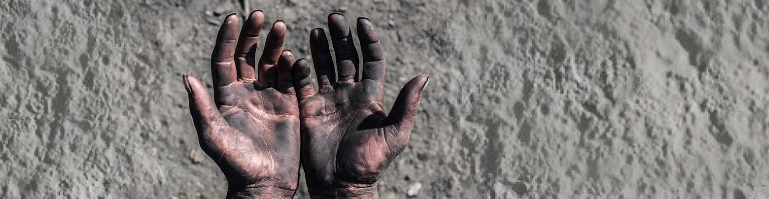 Bannière sur fond d'une photo de sable gris : on voit seulement deux mains réelles, tournées vers soi, tachées d'un minerai noir.